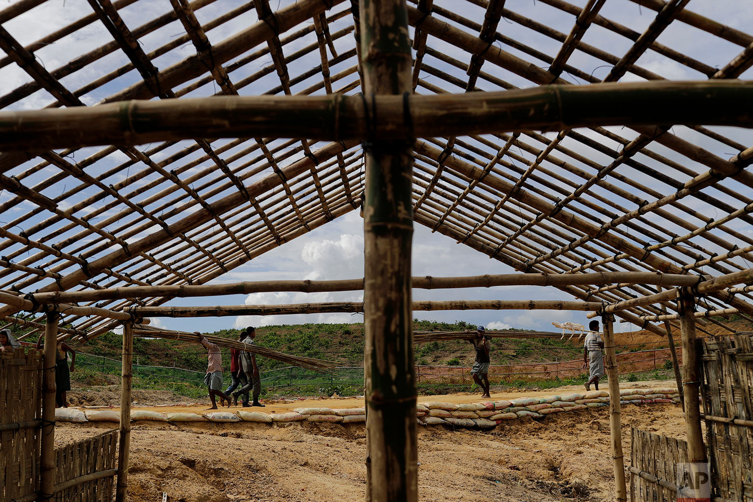 In this Thursday, June 28, 2018, photo, Rohingya refugees build new huts in an extended area of Kutupalong refugee camp in Bangladesh where some refugees living in areas considered at risk of landslides and flooding were relocated to.  (AP Photo/Wong Maye-E)