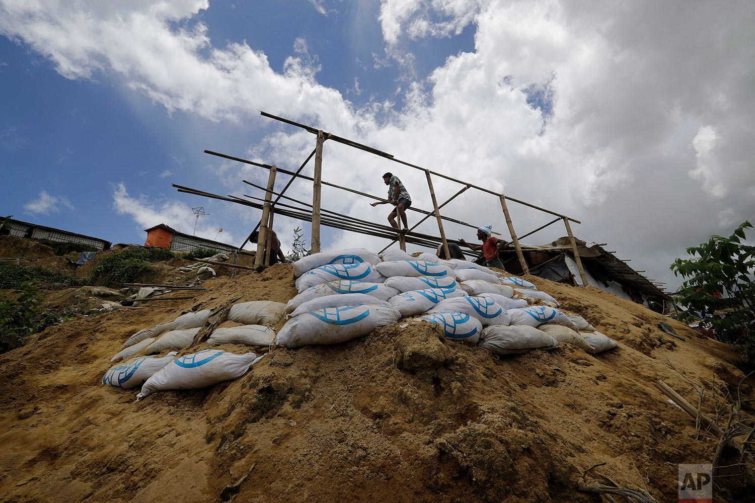 In this Thursday, June 28, 2018, photo, a man is silhouetted as he builds a new shelter for Mustawkima, who's former shelter was destroyed by heavy rains in Balukhali refugee camp, in Bangladesh. (AP Photo/Wong Maye-E)