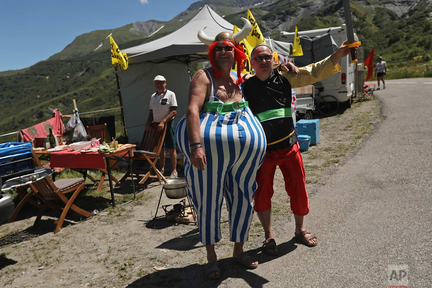 Two men dressed as French comics characters Asterix and Obelix line the road during the twelfth stage of the Tour de France cycling race over 175.5 kilometers (109 miles) with start in Bourg-Saint-Maurice Les Arcs and Alpe d'Huez, France, Thursday July 19, 2018. (AP Photo/Peter Dejong)