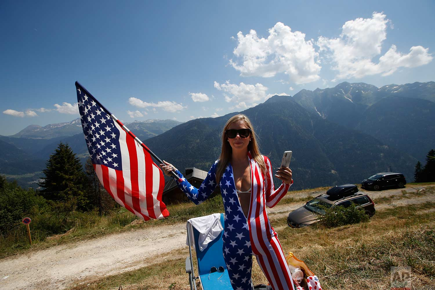 A cycling fan waits on the side of the road for riders to pass during the eleventh stage of the Tour de France cycling race over 108.5 kilometers (67.4 miles) with start in Albertville and finish in La Rosiere Espace San Bernardo, France. (AP Photo/Christophe Ena )