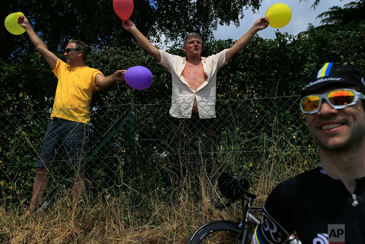 Spectators wait road-side for the pack to pass during the eight stage of the Tour de France cycling race over 181 kilometers (112.5 miles) with start in Dreux and finish in Amiens, France, Saturday, July 14, 2018.  (AP Photo/Peter Dejong)