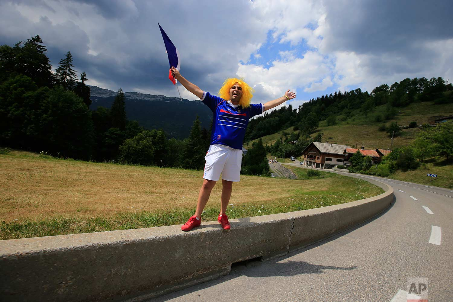 A cycling fan waves the French flag during the tenth stage of the Tour de France cycling race over 158.8 kilometers (98.7 miles) with start in Annecy and finish in Le Grand-Bornand, France, Tuesday, July 17, 2018. (AP Photo/Peter Dejong)