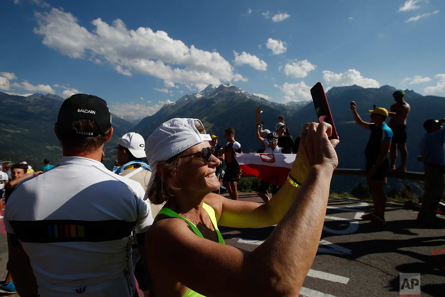 Fans wait in the French Alps for the riders too pass during the eleventh stage of the Tour de France cycling race over 108.5 kilometers (67.4 miles) with start in Albertville and finish in La Rosiere Espace San Bernardo, France. (AP Photo/Christophe Ena )