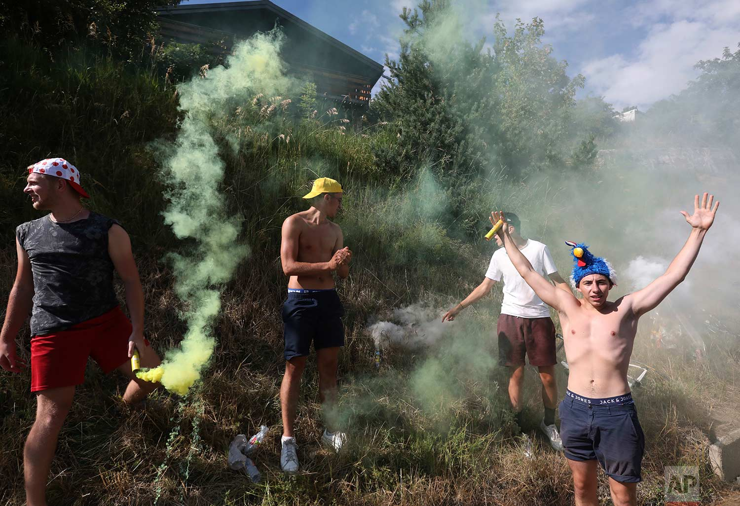 Fans set off flares as the group of leaders passes during the twelfth stage of the Tour de France cycling race over 175.5 kilometers (109 miles) with start in Bourg-Saint-Maurice Les Arcs and Alpe d'Huez, France, Thursday July 19, 2018. (AP Photo/Peter Dejong)