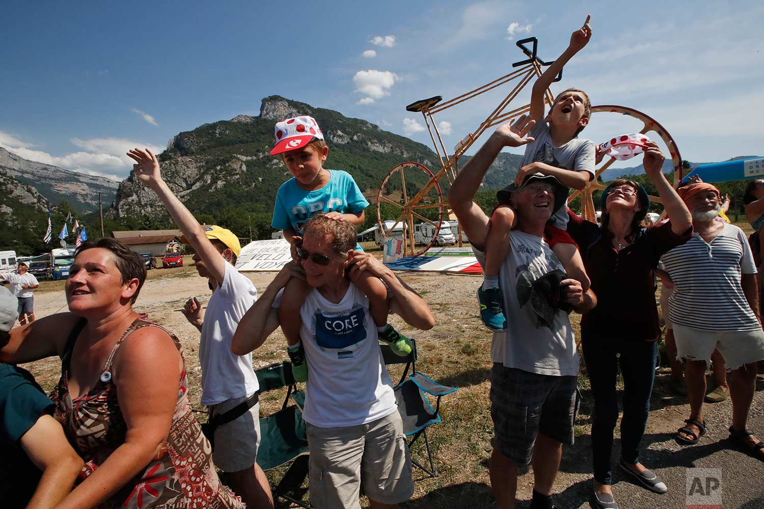 Fans lining the road look up at helicopters passing overhead during the thirteenth stage of the Tour de France cycling race over 169.5 kilometers (105.3 miles) with start in Bourg d'Oisans and finish in Valence, France, Friday July 20, 2018. (AP Photo/Christophe Ena )