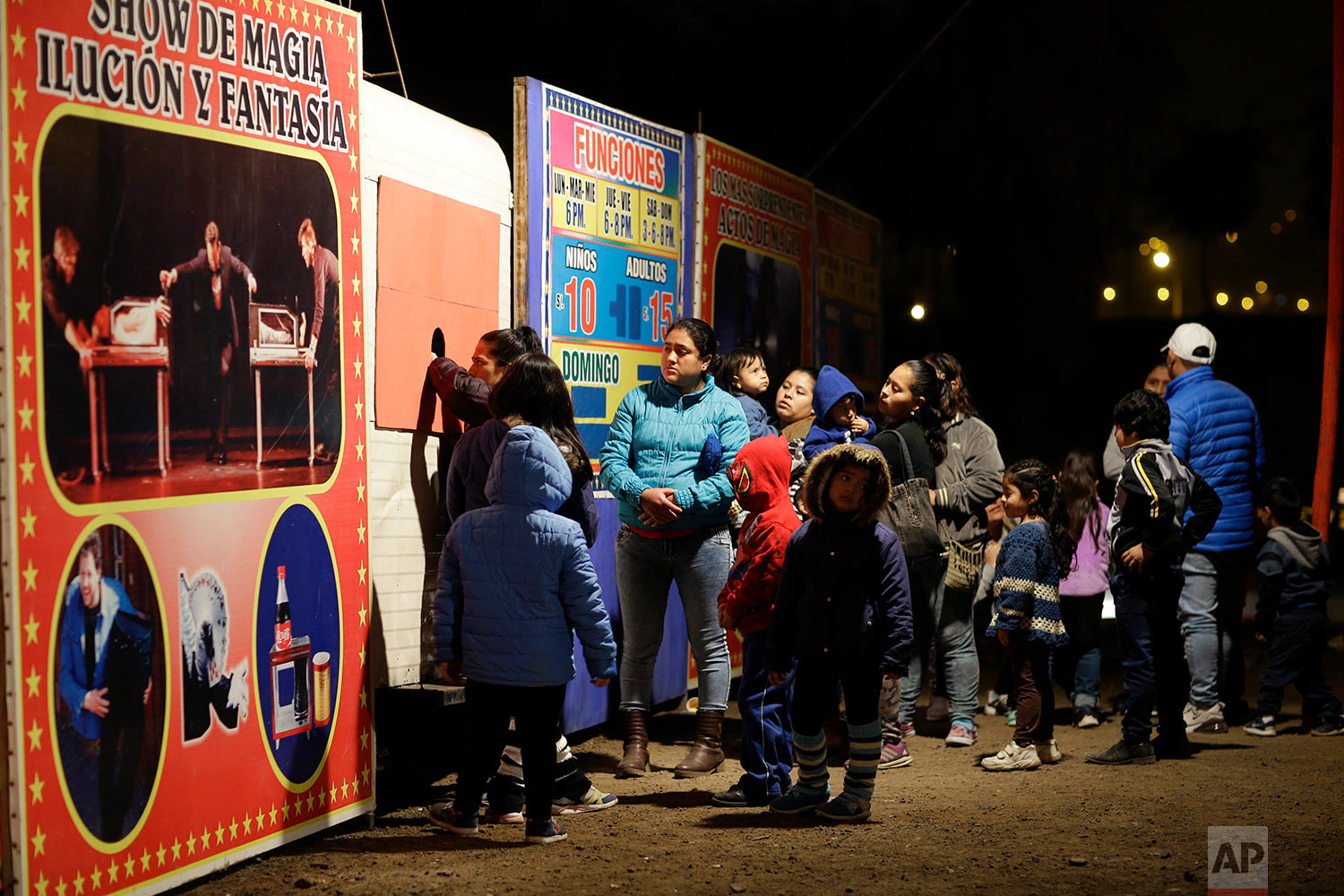 "People buy tickets to enter a show by the International Circus set up in the shantytown of Pro on the outskirts of Lima, Peru, July 20, 2018. The billboard reads in Spanish ""Show of magic, illusion and fantasy."" (AP Photo/Martin Mejia)"