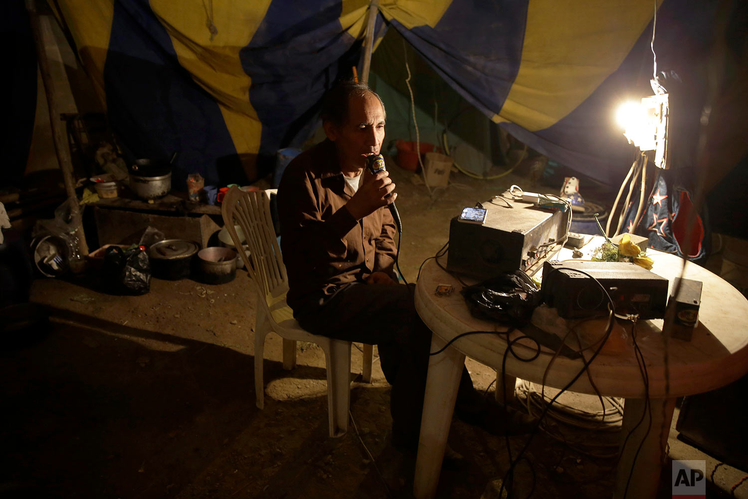 Circus owner and clown Jose Alvarez talks into a loud speaker system to announce the soon-to-start opening act, from the circus tent set up in the shantytown of Puente Piedra on the outskirts of Lima, Peru, July 8, 2018. (AP Photo/Martin Mejia)