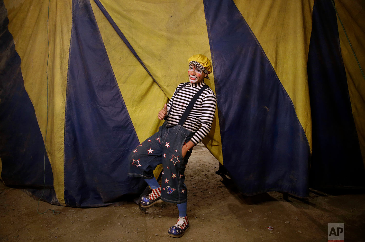 "Santiago Astopilco, dressed as his clown personality ""Vaguito"" poses for a portrait behind the Tony Perejil circus tent set up in the shantytown of Puente Piedra, before the start of the show on the outskirts of Lima, Peru, July 8, 2018. (AP Photo/Martin Mejia)"