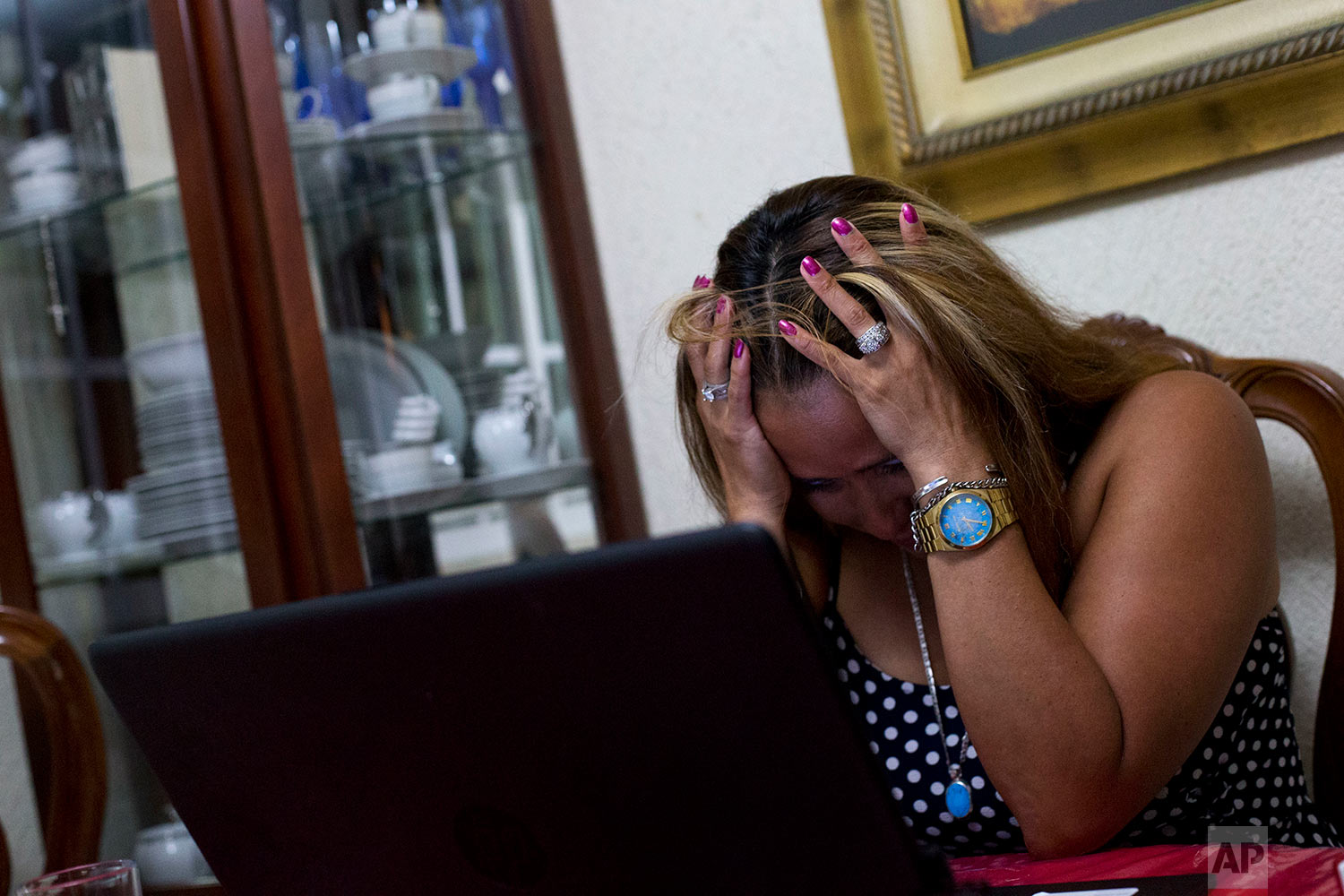 Letty Stegall is overwhelmed by emotion after talking to her daughter and watching the security cameras at the bar she manages back in Kansas City, Mo., as she sits at a table in her parents' home in Boca Del Rio, Veracruz state, Mexico. (AP Photo/Rebecca Blackwell)