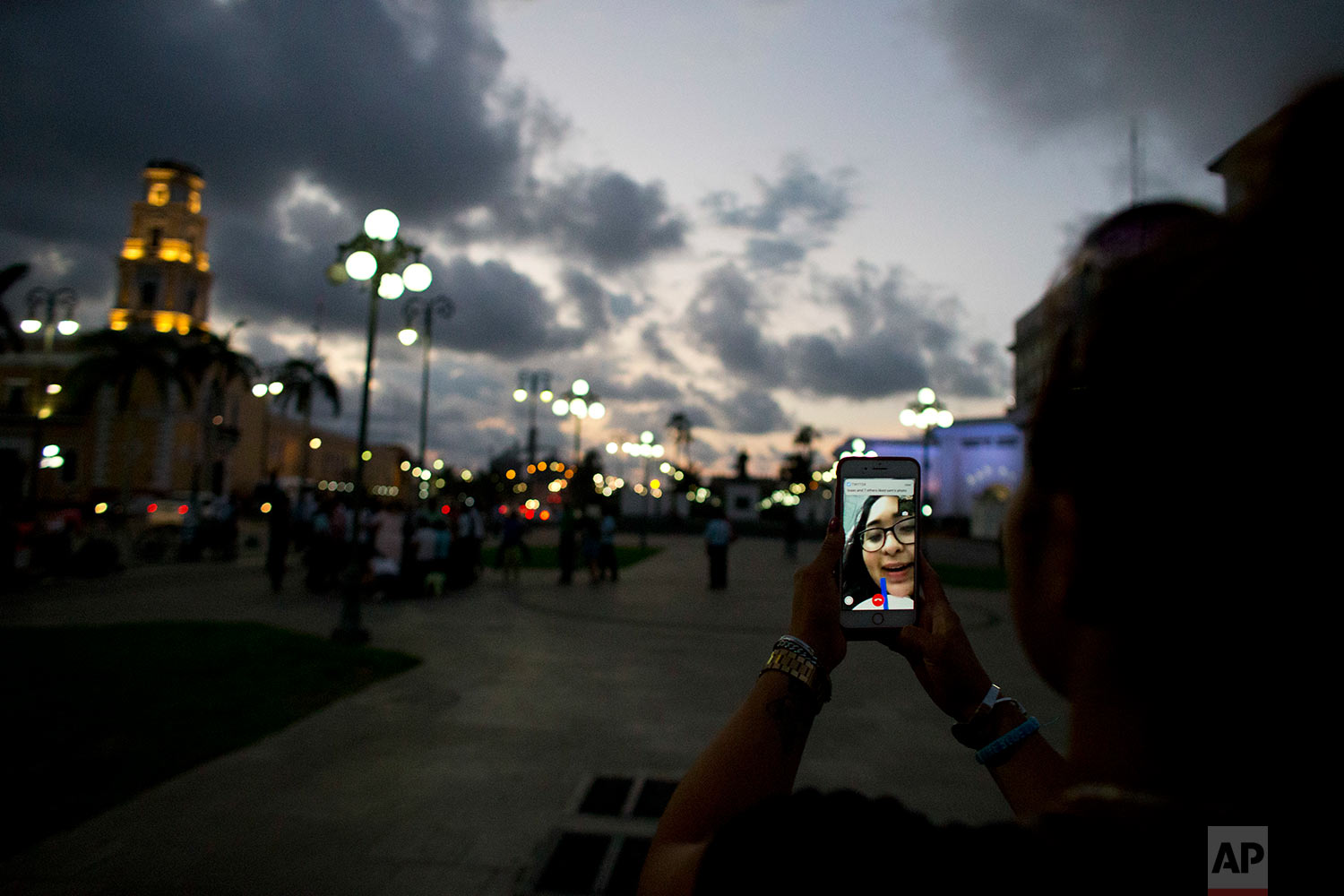 Letty Stegall speaks with her daughter on a video call as she walks near the port in Veracruz, Mexico. (AP Photo/Rebecca Blackwell)