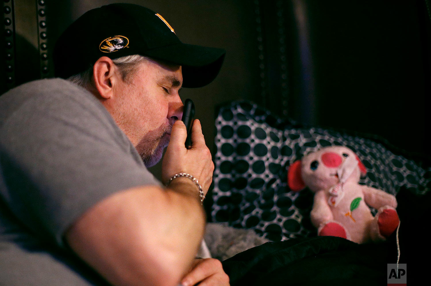 Steve Stegall shares the phone with his stepdaughter, Jennifer, while making a video call with his wife, Letty. (AP Photo/Charlie Riedel)