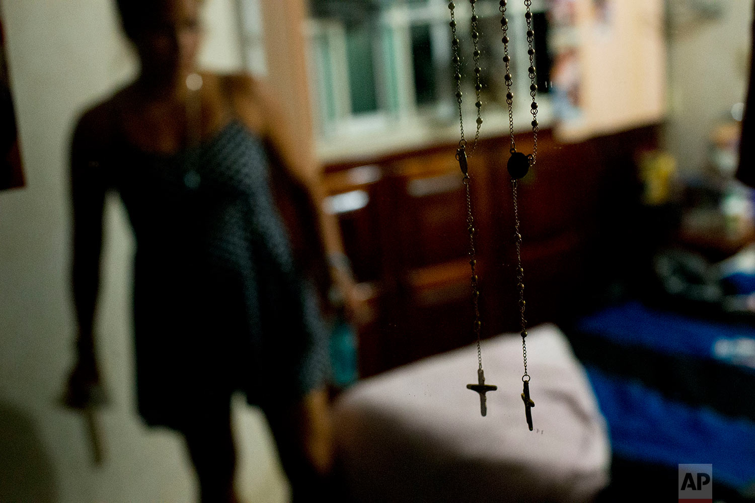 Rosaries hang on a mirror in the bedroom where Letty Stegall is staying in her parents' home in Boca Del Rio, Veracruz state, Mexico. (AP Photo/Rebecca Blackwell)