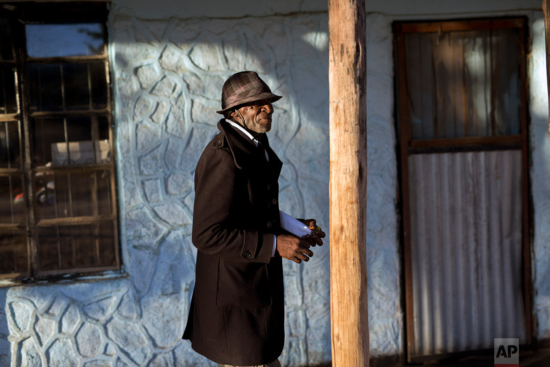 Men gather in the village of Silozwi in the Matobo hills in Zimbabwe. (AP Photo/Jerome Delay)