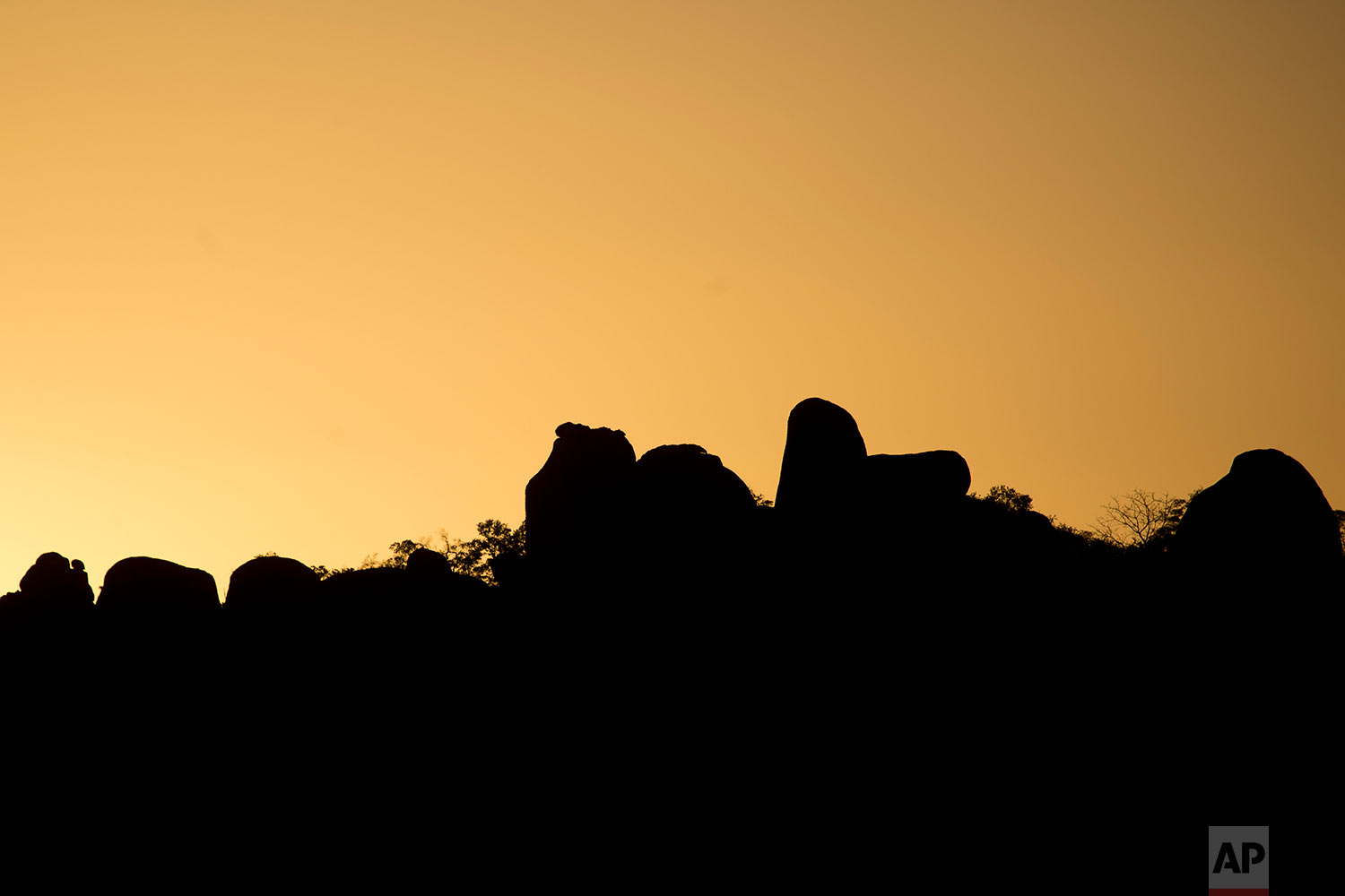 The sun sets over the Matobo hills where, over 30 years ago, Zimbabwe army soldiers killed in what many called the Matabeleland Massacres, or Gukurahundi. (AP Photo/Jerome Delay)