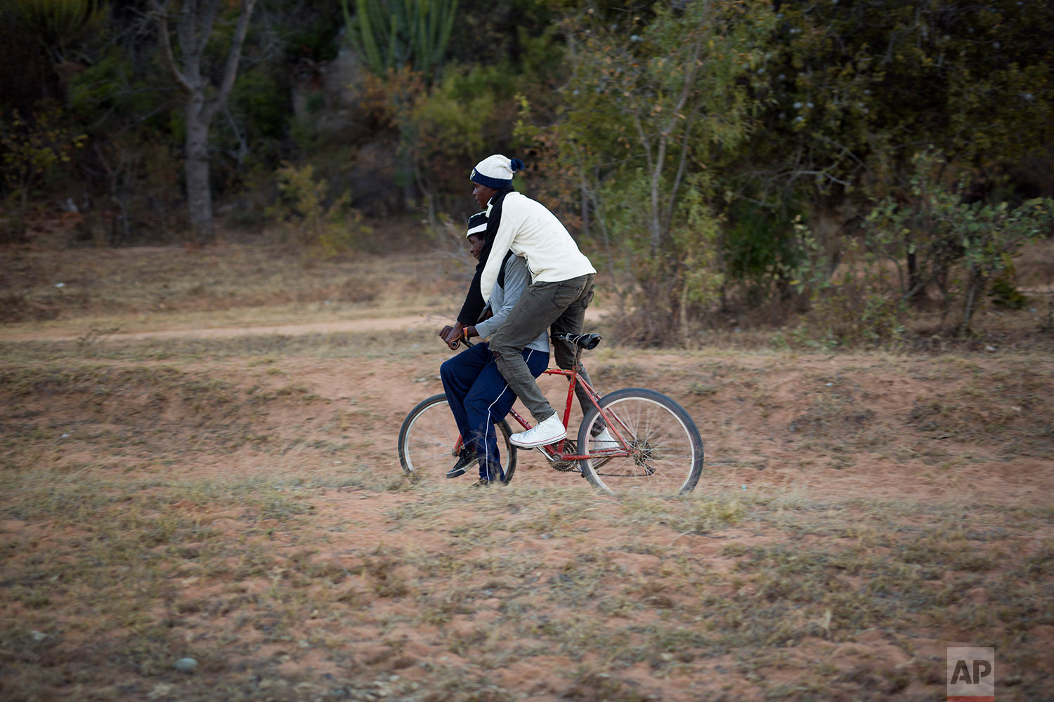 Men ride a bicycle near the village of Silozwi in the Matobo hills in Zimbabwe.(AP Photo/Jerome Delay)