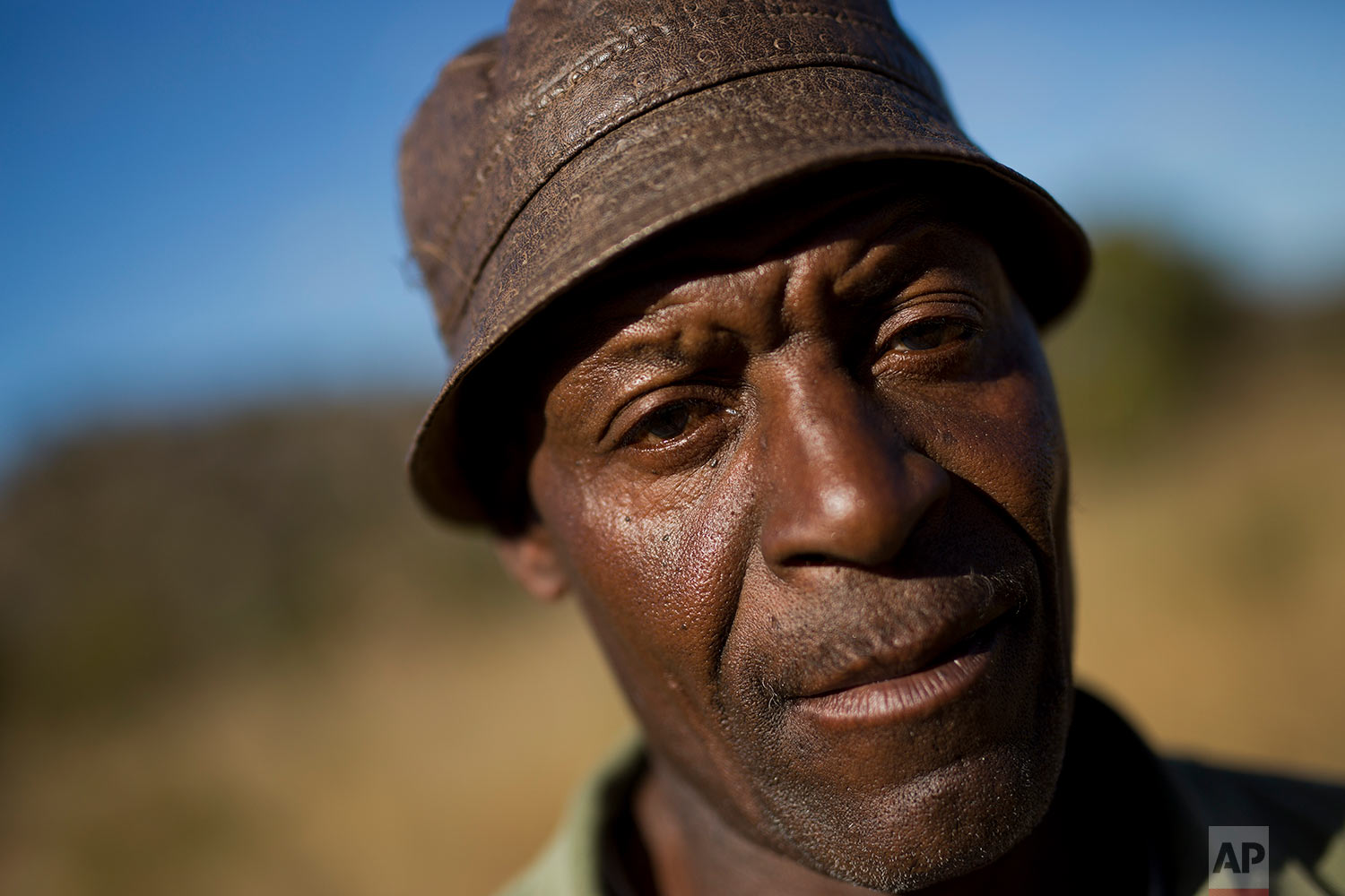 Isaiah Nkomo poses in his fields near the village of Whitewater in the Matobo hills in Zimbabwe. Nkomo has been looking for his missing brother Simimba for over 30 years. Simimba fell victim of Zimbabwean soldiers during the Matabeleland Massacres. (AP Photo/Jerome Delay)