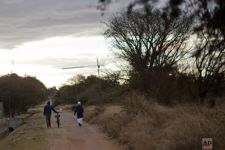 A couple walks back from church in Bulawayo, Zimbabwe. (AP Photo/Jerome Delay)