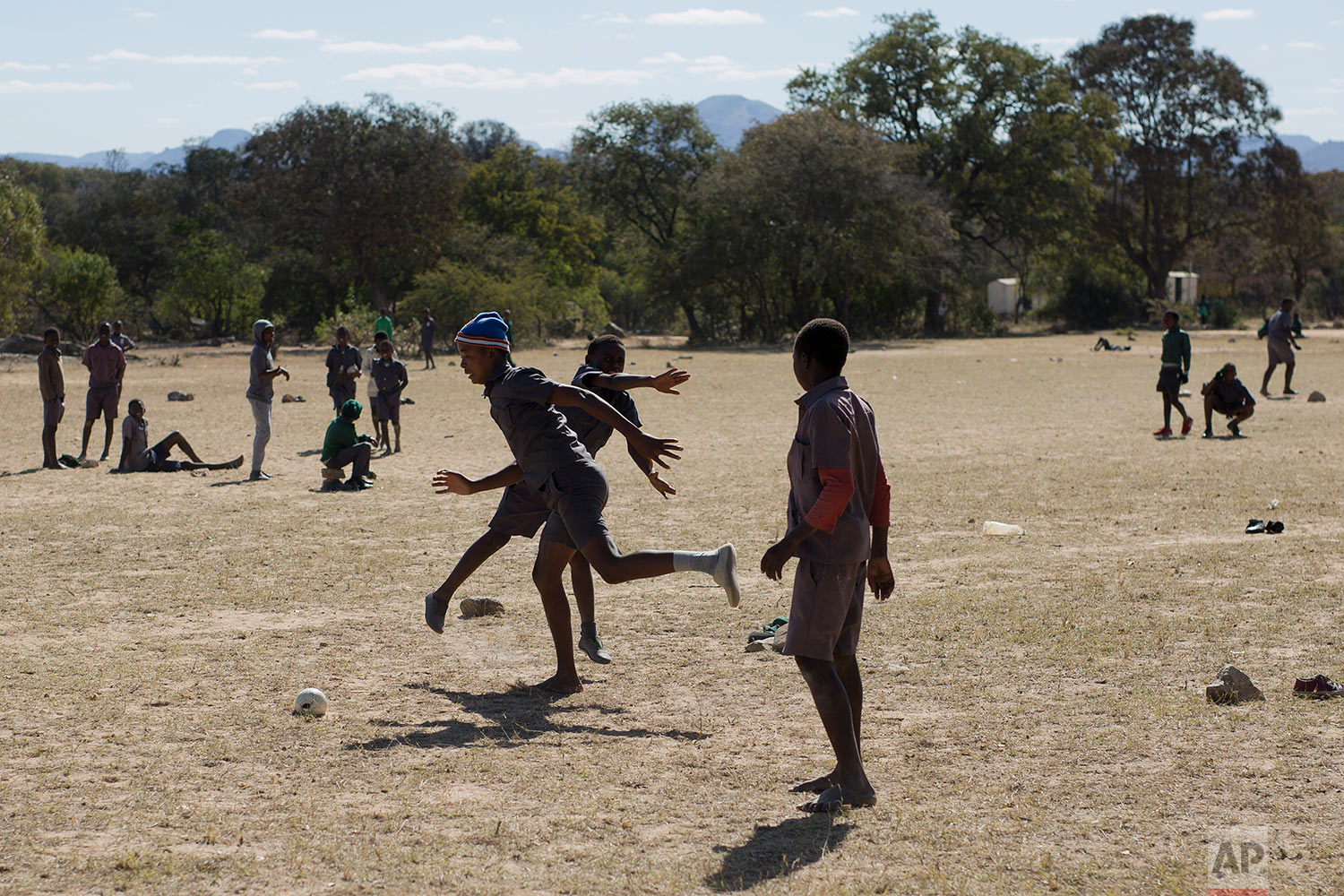 School children play football in the school playground in Simbumbumbu, Zimbabwe, the very place where Ellis Ndlovu's son Edwel was killed 34 years ago by Zimbabwe army soldiers in what many called the Matabeleland Massacres, or Gukurahundi. (AP Photo/Jerome Delay)