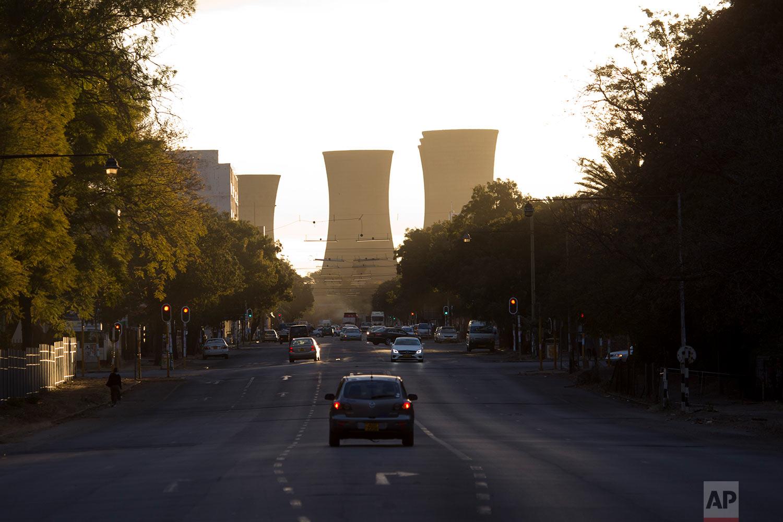 The sun sets on cooking towers downtown Bulawayo, Zimbabwe.(AP Photo/Jerome Delay)