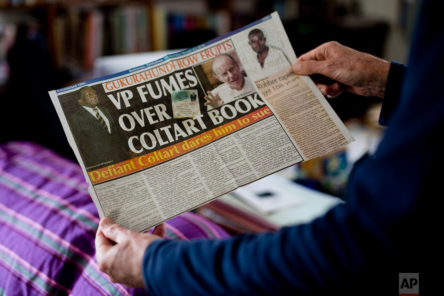 Human rights lawyer and opposition candidate in the July 30 legislative elections David Coltart holds a newspaper clipping in his Bulawayo, Zimbabwe residence. (AP Photo/Jerome Delay)
