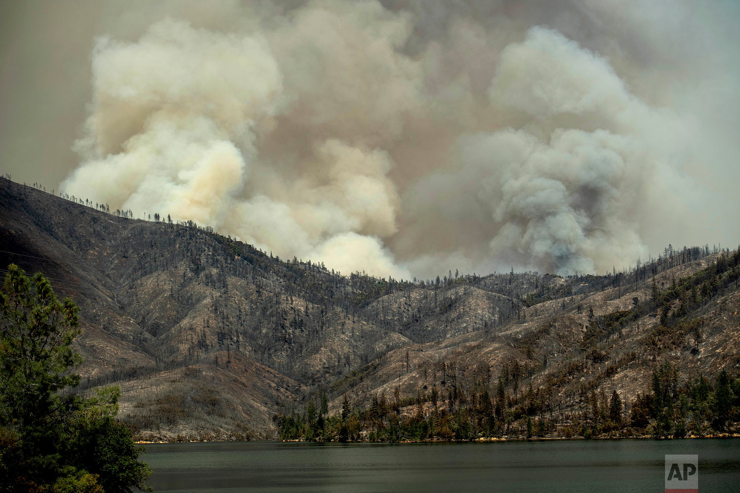 The Carr Fire burns above Whiskeytown Lake near Whiskeytown, Calif., on Thursday, July 26, 2018. (AP Photo/Noah Berger)