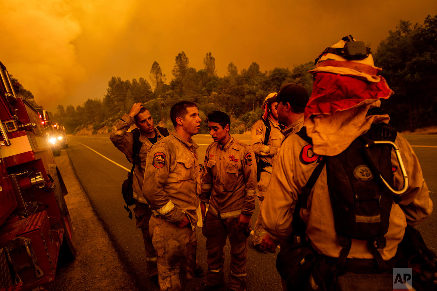 Firefighters discuss plans while battling the Carr Fire in Shasta, Calif., on Thursday, July 26, 2018. (AP Photo/Noah Berger)