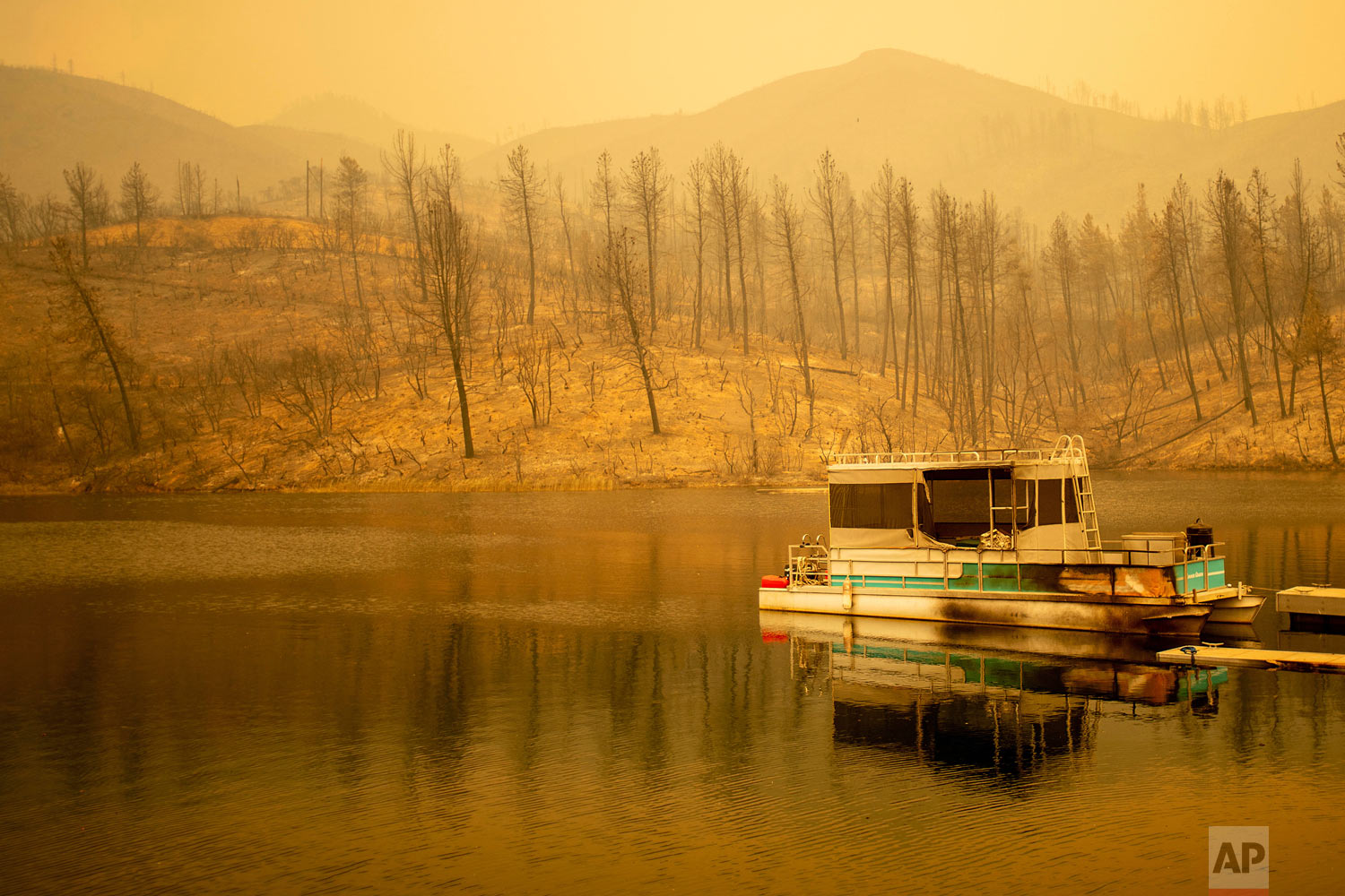A boat scorched by the Carr Fire floats on Whiskeytown Lake in Whiskeytown, Calif., on Friday, July 27, 2018. The flames moved so fast that firefighters working in oven-like temperatures and bone-dry conditions had to drop efforts to battle the blaze at one point to help people escape. (AP Photo/Noah Berger)