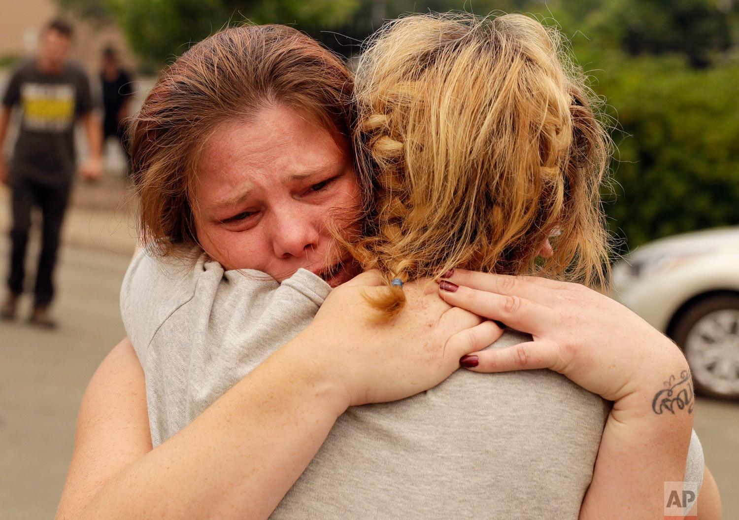 Carla Bledsoe, facing camera, hugs her sister, Sherry, outside of the sheriff's office in Redding, Calif., on Saturday, July 28, 2018, after hearing news that Sherry's children, James and Emily, and her grandmother, Melody Bledsoe, were killed in a wildfire. (AP Photo/Marcio Jose Sanchez)