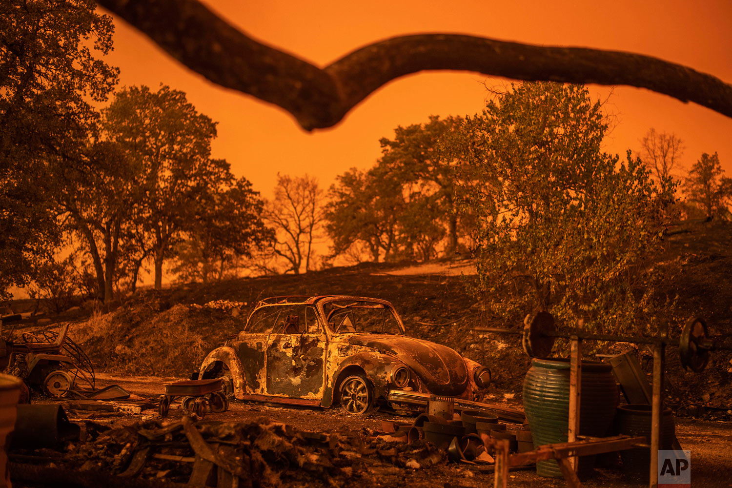 A Volkswagen Beetle scorched by a wildfire called the Carr Fire rests at a residence in Redding, Calif., Friday, July 27, 2018. The wildfire roared with little warning into the Northern California city as thousands of people scrambled to escape before the walls of flames descended from forested hills onto their neighborhoods, officials said Friday. (AP Photo/Noah Berger)