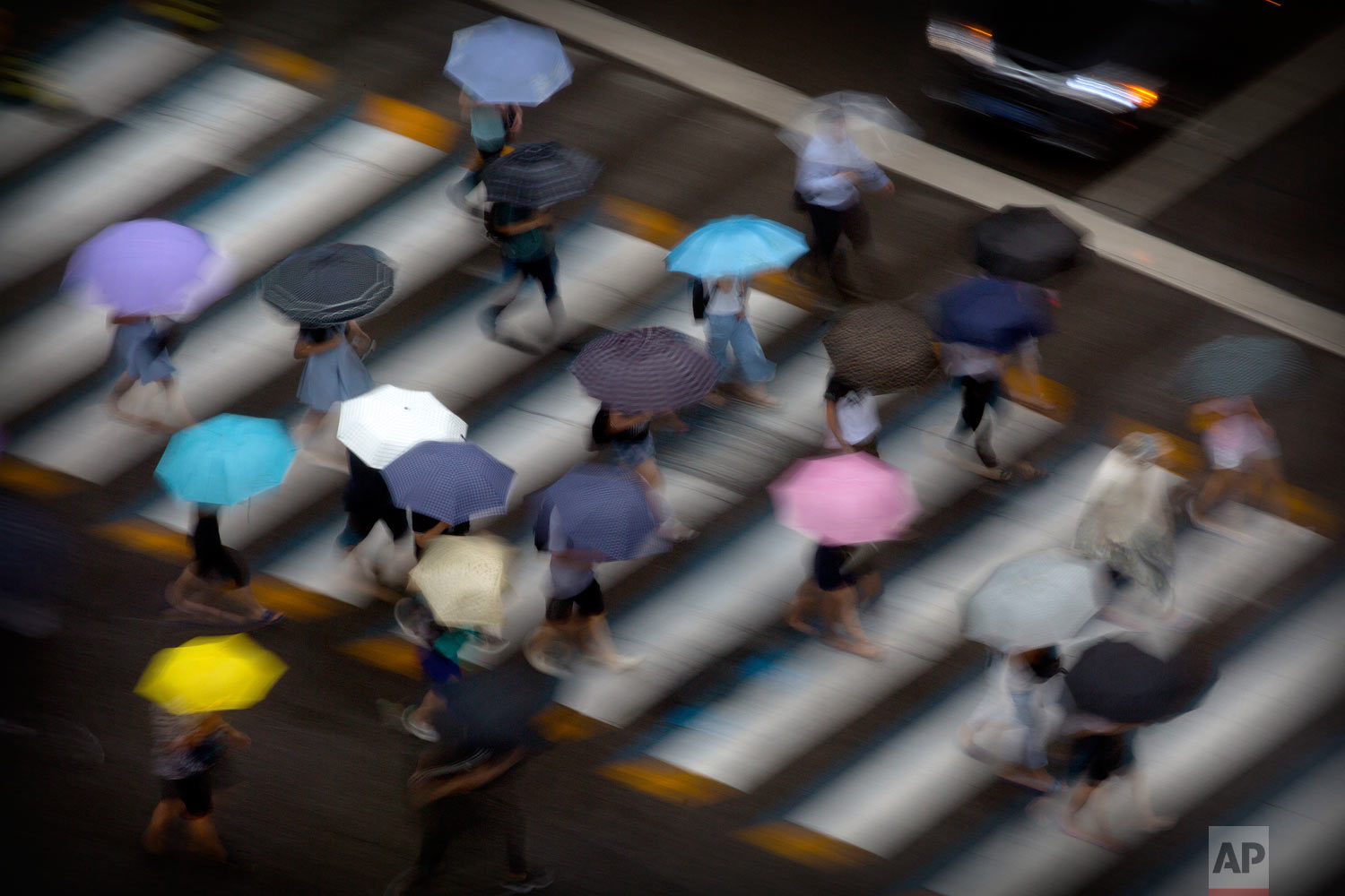 In this photo taken with a long exposure, pedestrians carry umbrellas as they cross a street in Beijing, Tuesday, July 24, 2018. The remnants of Typhoon Ampil brought heavy rain to China's capital on Tuesday morning. (AP Photo/Mark Schiefelbein)