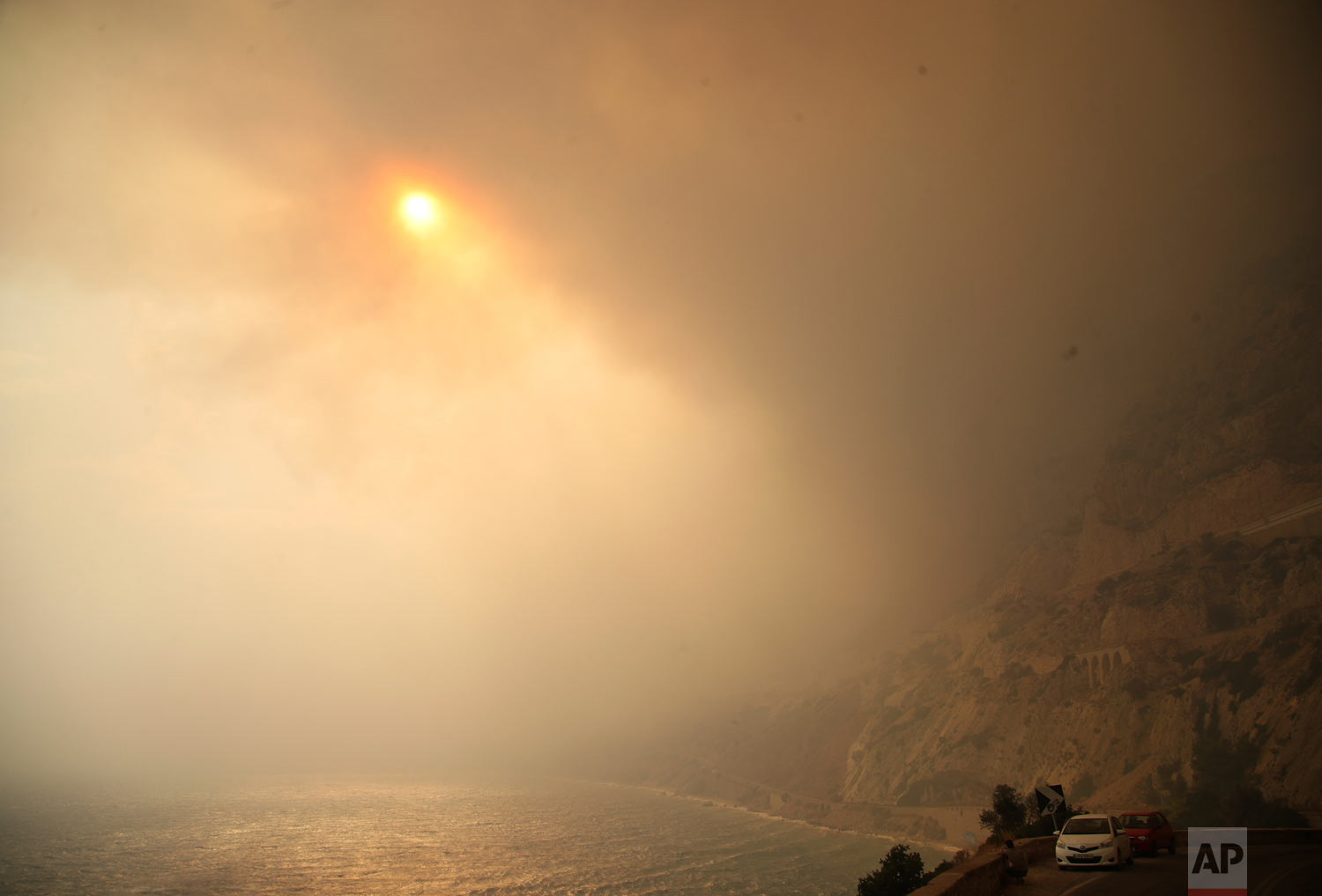 The sun breaks through a smoked-filled sky as cars drive on a road near Kineta, west of Athens, Monday, July 23, 2018. As of Friday, at least 86 people have been killed in the wildfires near the capital. (AP Photo/Thanassis Stavrakis)