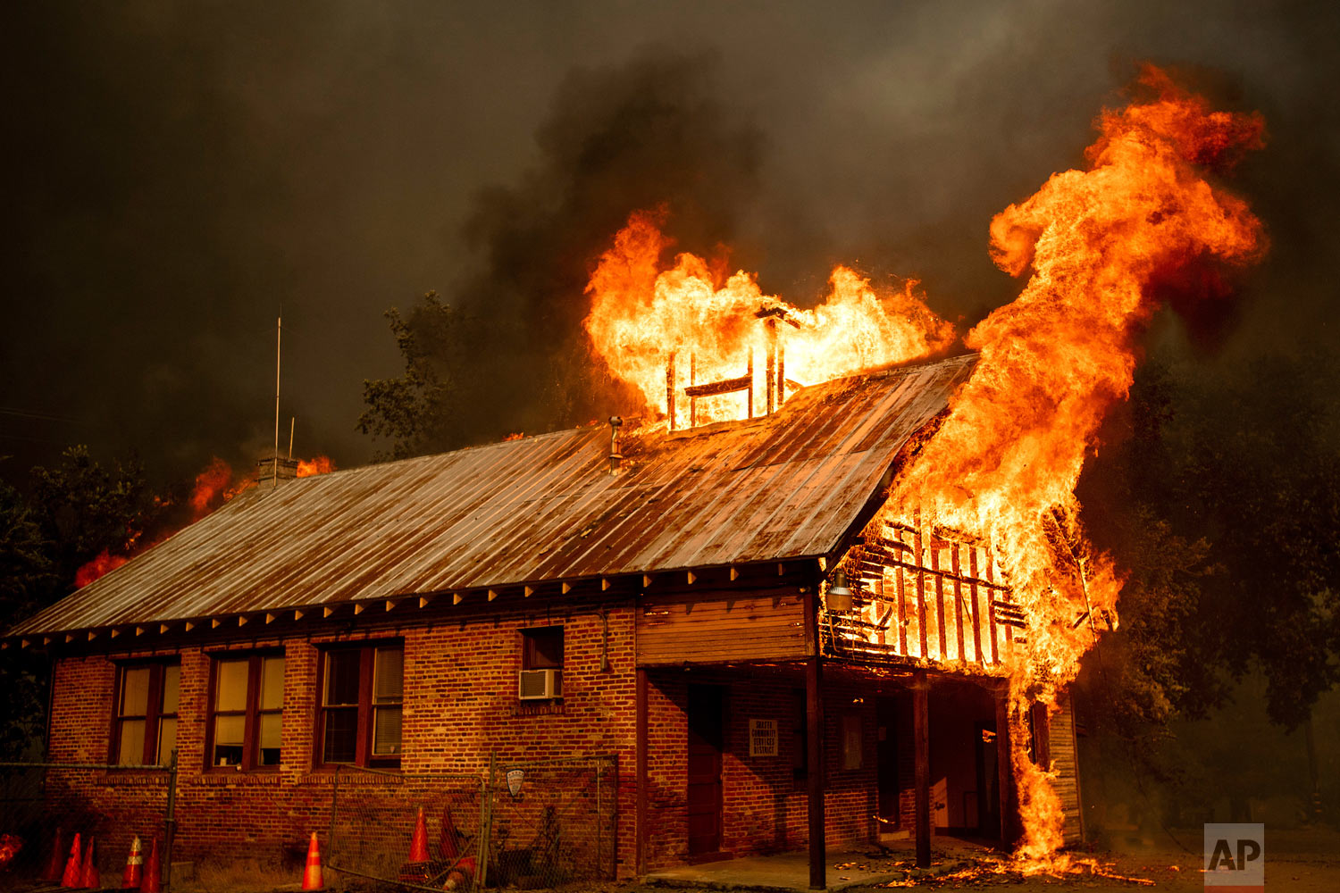 An historic schoolhouse burns as the Carr Fire tears through Shasta, Calif., Thursday, July 26, 2018. The wildfires have been fueled by high temperatures, wind and low humidity in the area. (AP Photo/Noah Berger)
