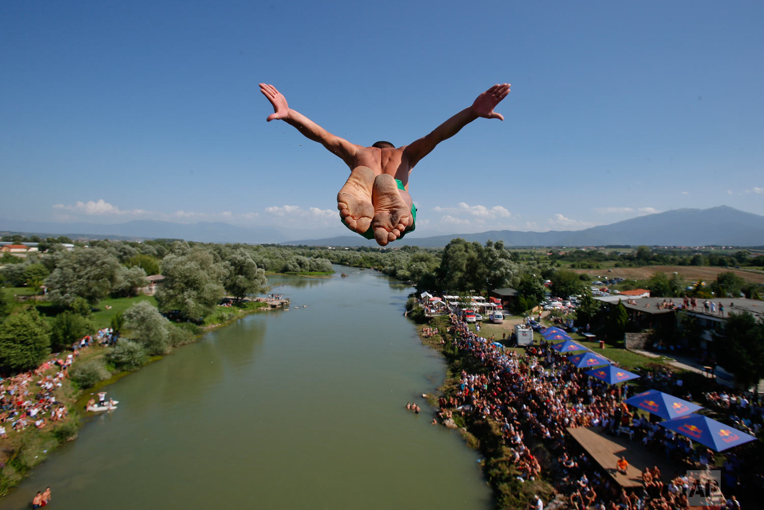 Spectators watch from the river banks as a diver launches from the Ura e Shejnt bridge during the 68th annual high diving competition, near the town of Gjakova, Kosovo on Sunday, July 22, 2018. (AP Photo/Visar Kryeziu)