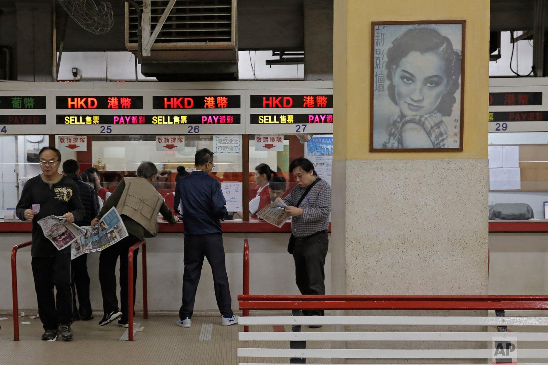 Gamblers place bets on races at the Macau Yat Yuen Canidrome in Macau.(AP Photo/Kin Cheung)