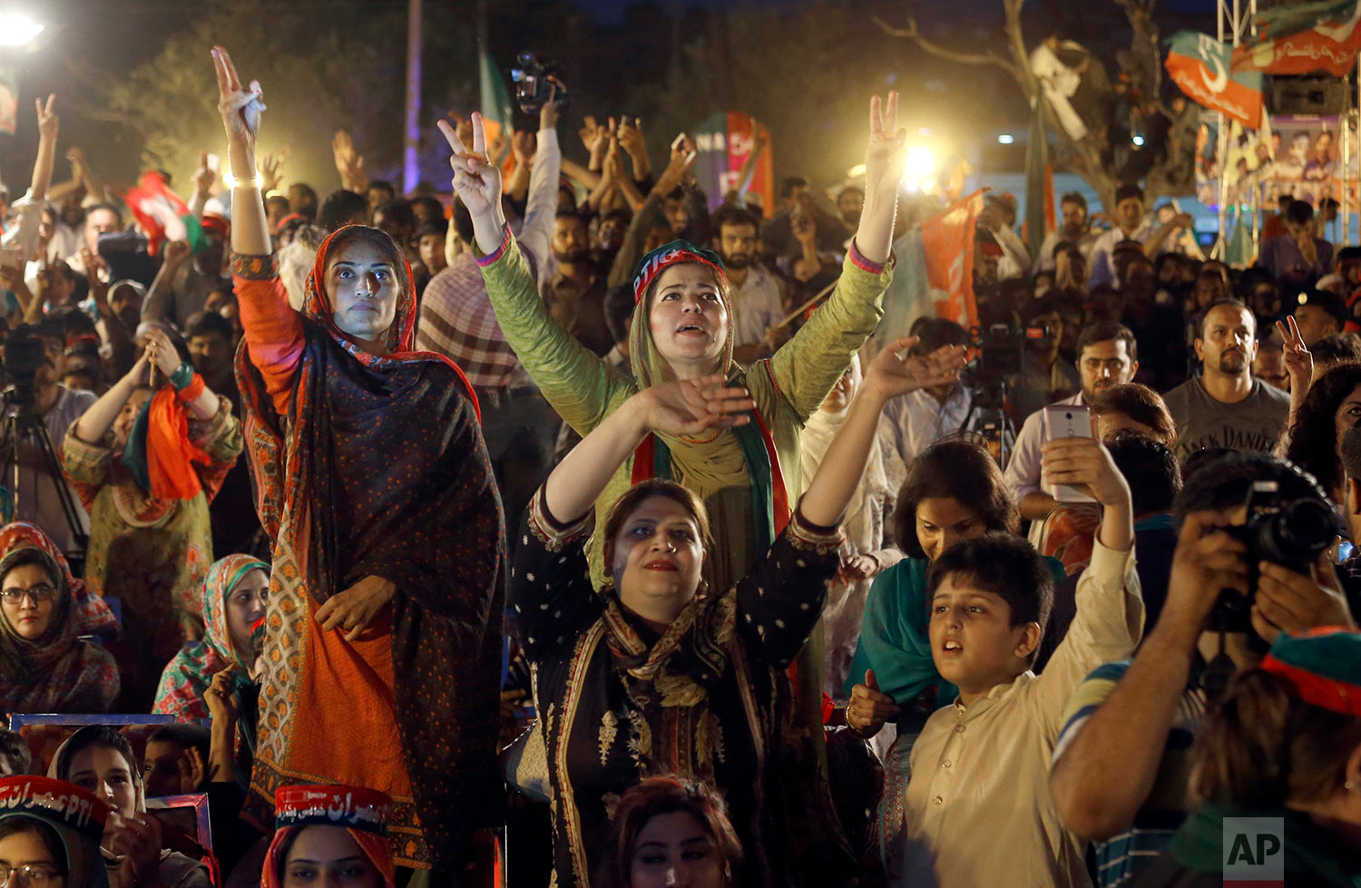 Supporters of Tehreek-e-Insaf party greet to their leader Imran Khan during an election campaign rally in Islamabad, Pakistan, Saturday, July 21, 2018. (AP Photo/Anjum Naveed)