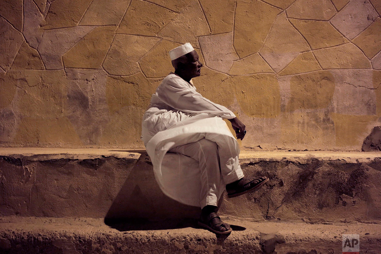 65-year old Mohammed Haroun sits in front of his home in Wadi Karkar, a new complex under construction in the desert west of Lake Nasser, Aswan, Egypt on May 7, 2018. Evicted from their ancestral lands to make way for the world's largest man-made lake behind the Aswan Dam, Egypt's Nubians have found both pain and nostalgia in memories of the peaceful and uncorrupted life they once had. (AP Photo/Nariman El-Mofty)
