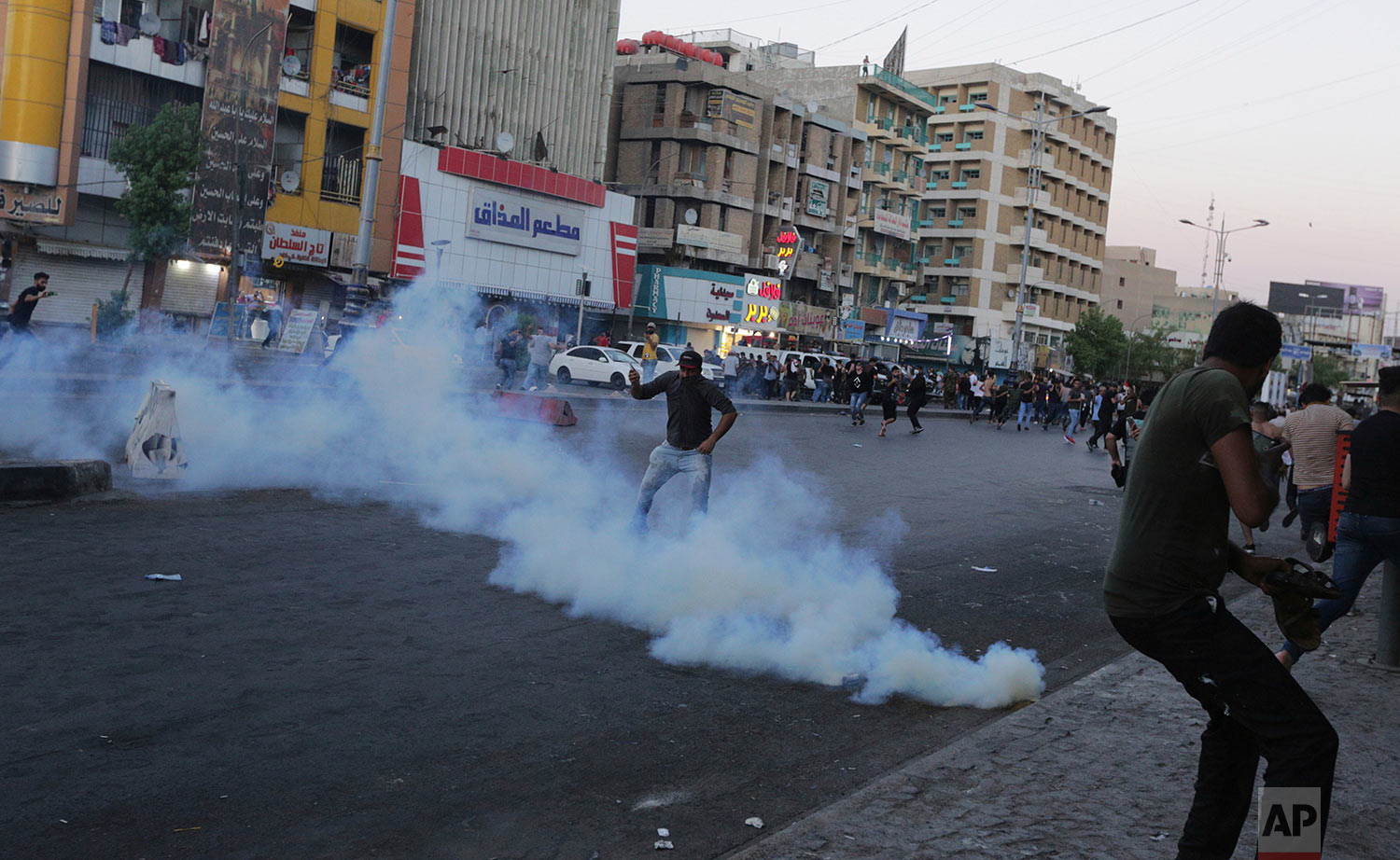 Iraq protesters demanding better public services and jobs run from tear gas fired by security forces, during a demonstration in Tahrir Square in central Baghdad, Iraq, Friday, July 20, 2018. (AP Photo/Hadi Mizban)