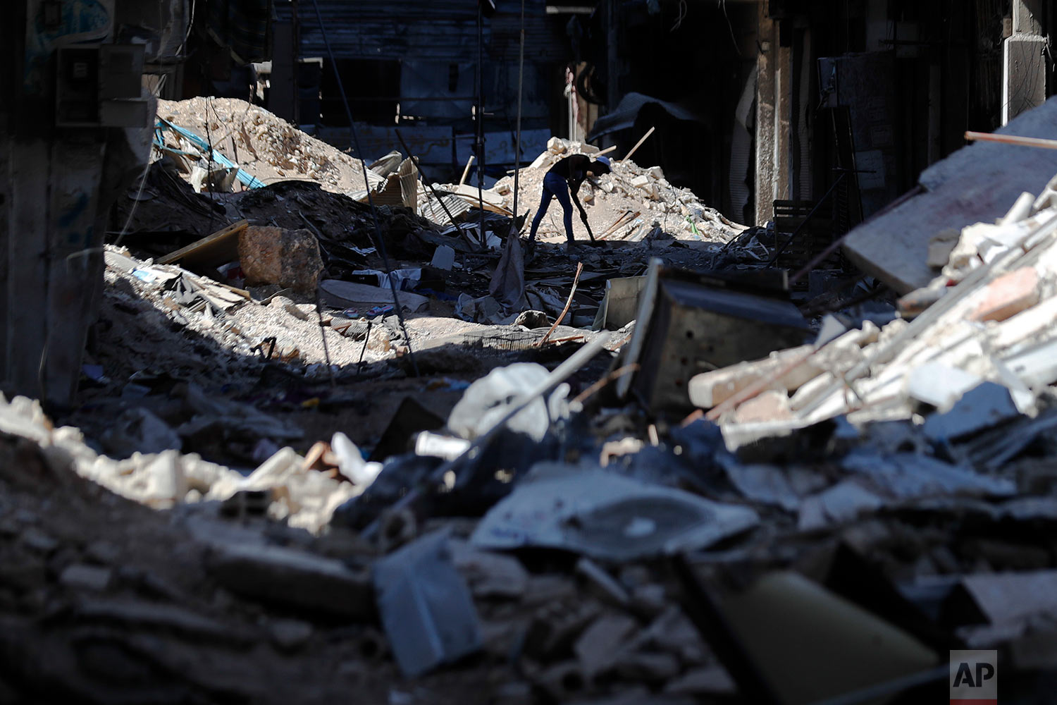 A young man removes rubble in front of his shop in the Palestinian refugee camp of Yarmouk in the Syrian capital Damascus, Syria, Monday, July 16, 2018. (AP Photo/Hassan Ammar)