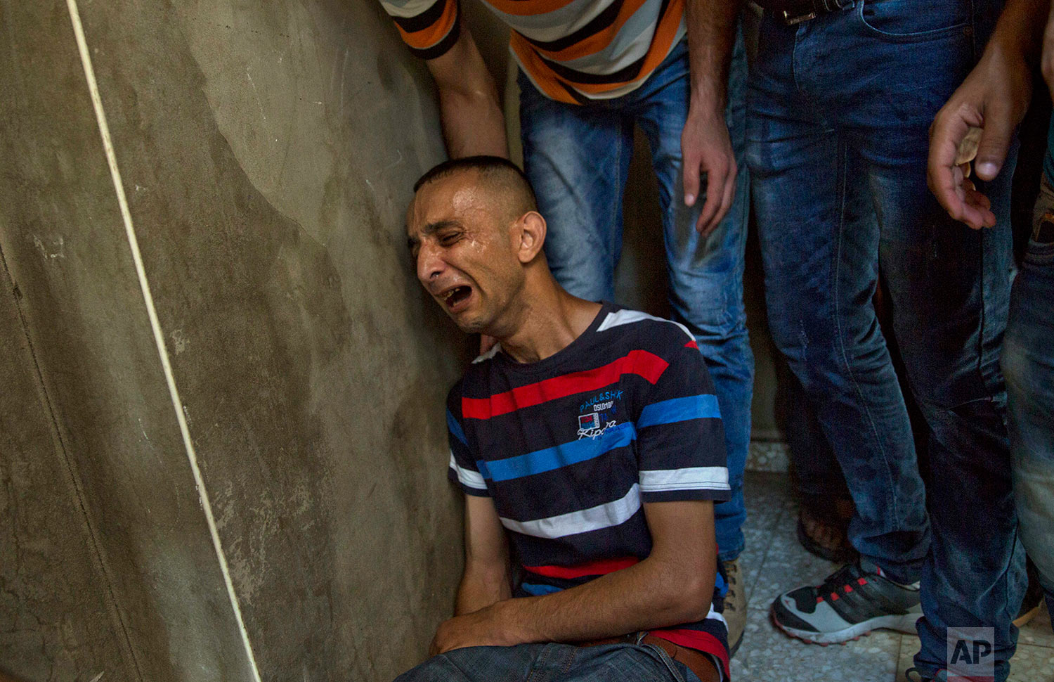 A Palestinian relative of Mohammed Badwan, 27, who was shot and killed by Israeli troops on Friday's ongoing protest at the Gaza Strip's border with Israel, mourns at the family home during his funeral in Gaza City, Saturday, July 21, 2018. (AP Photo/Khalil Hamra)
