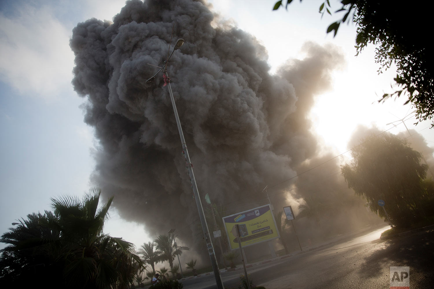 Smoke raises in the background following an Israeli airstrike hits a governmental building in Gaza City , Saturday, July 14, 2018.(AP Photo/Khalil Hamra)