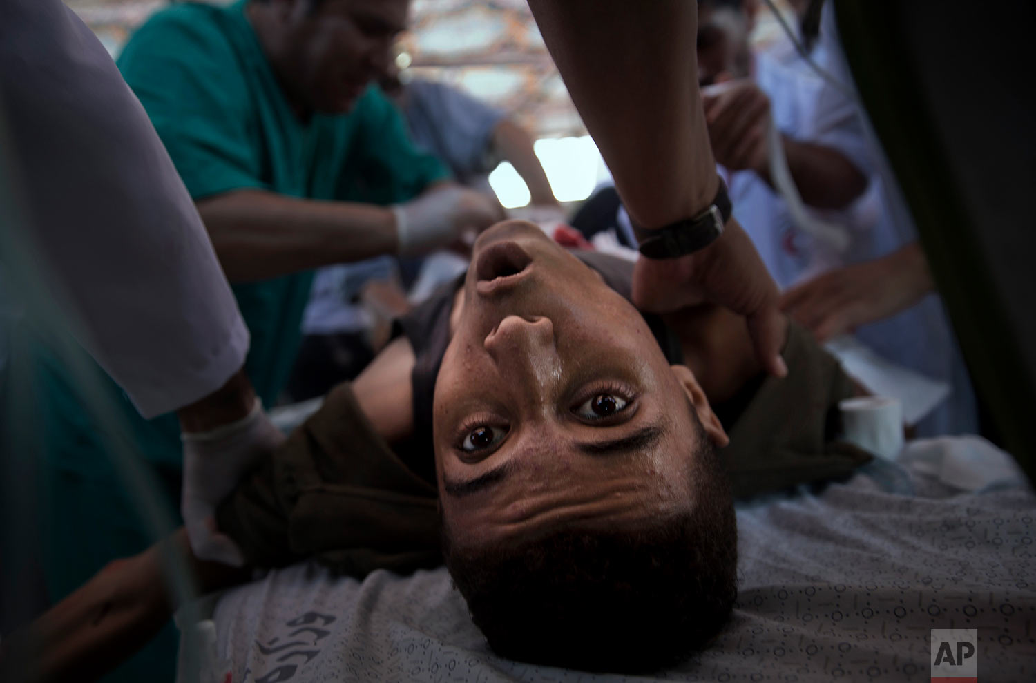 An injured Palestinian youth receives treatment in a field clinic after being shot by Israeli troops during a protest at the Gaza Strip's border with Israel, Friday, July 20, 2018.(AP Photo/Khalil Hamra)