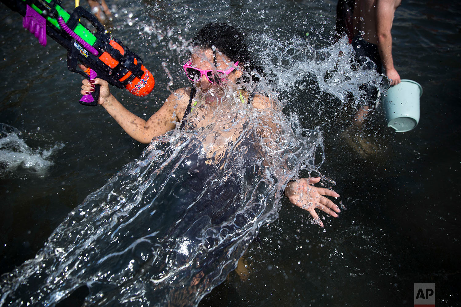 People spray water during a water fight club event attended by several hundred people, and held annually to mark the start of the summer vacation, at Habima Square, in central Tel Aviv, Israel, Friday, July 6, 2018. (AP Photo/Oded Balilty)