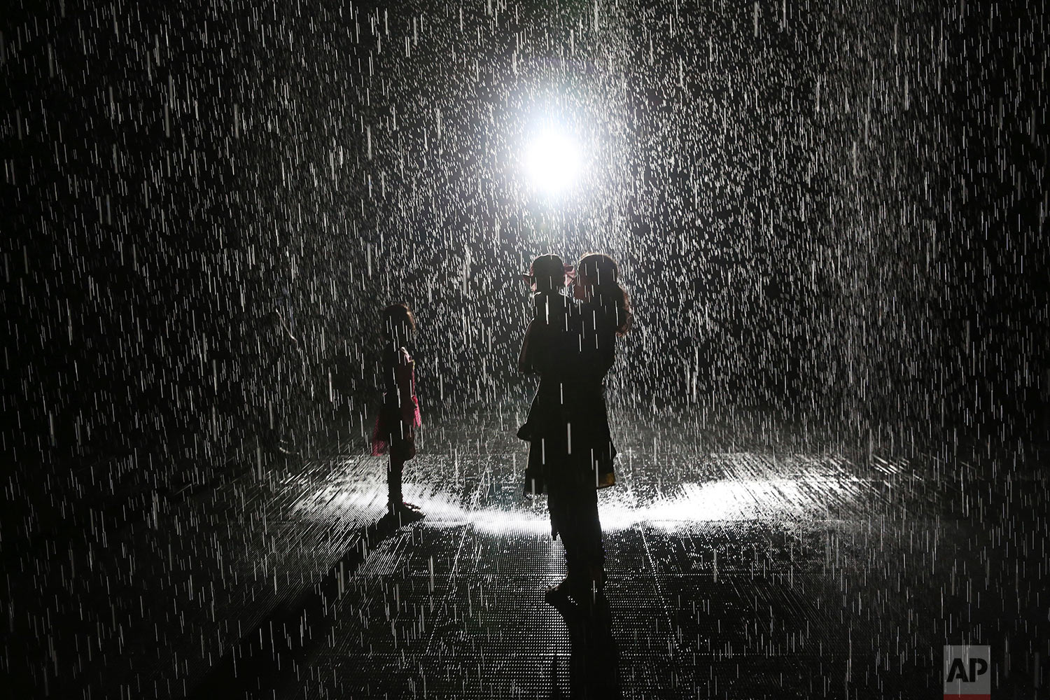 """Visitors walk through the Sharjah Art Foundation's """"Rain Room"""" installation in Sharjah, United Arab Emirates, Sunday, July 22, 2018. The art installation uses motion sensors to allow visitors to walk through it without getting wet as 2,500 liters of self-cleaning recycled water fall. (AP Photo/Jon Gambrell)"""
