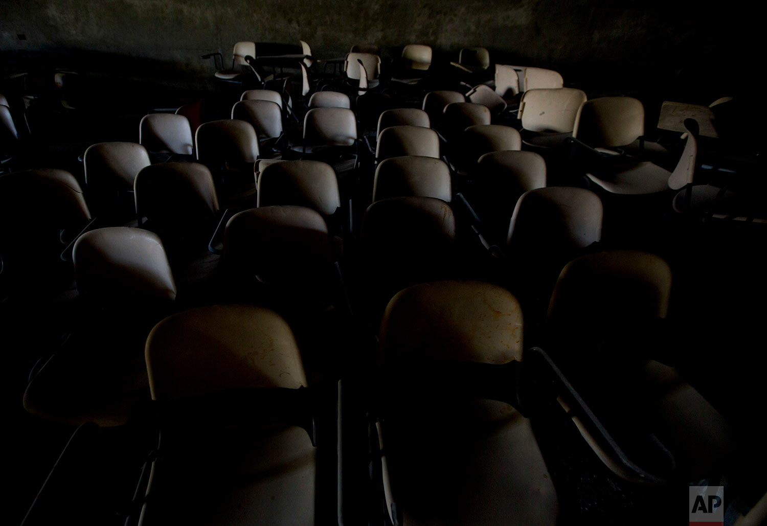 Stacked delegates' chairs are seen in an underground garage of what was to be a Palestinian parliament in Abu Dis, West Bank on  June 24, 2018. This decrepit building, built during the heyday of Israeli-Palestinian peace talks in the 1990s, was meant to serve the Palestinian parliament. Today, it is a grim reminder of dashed Mideast peace hopes and what might have been. (AP Photo/Dusan Vranic)