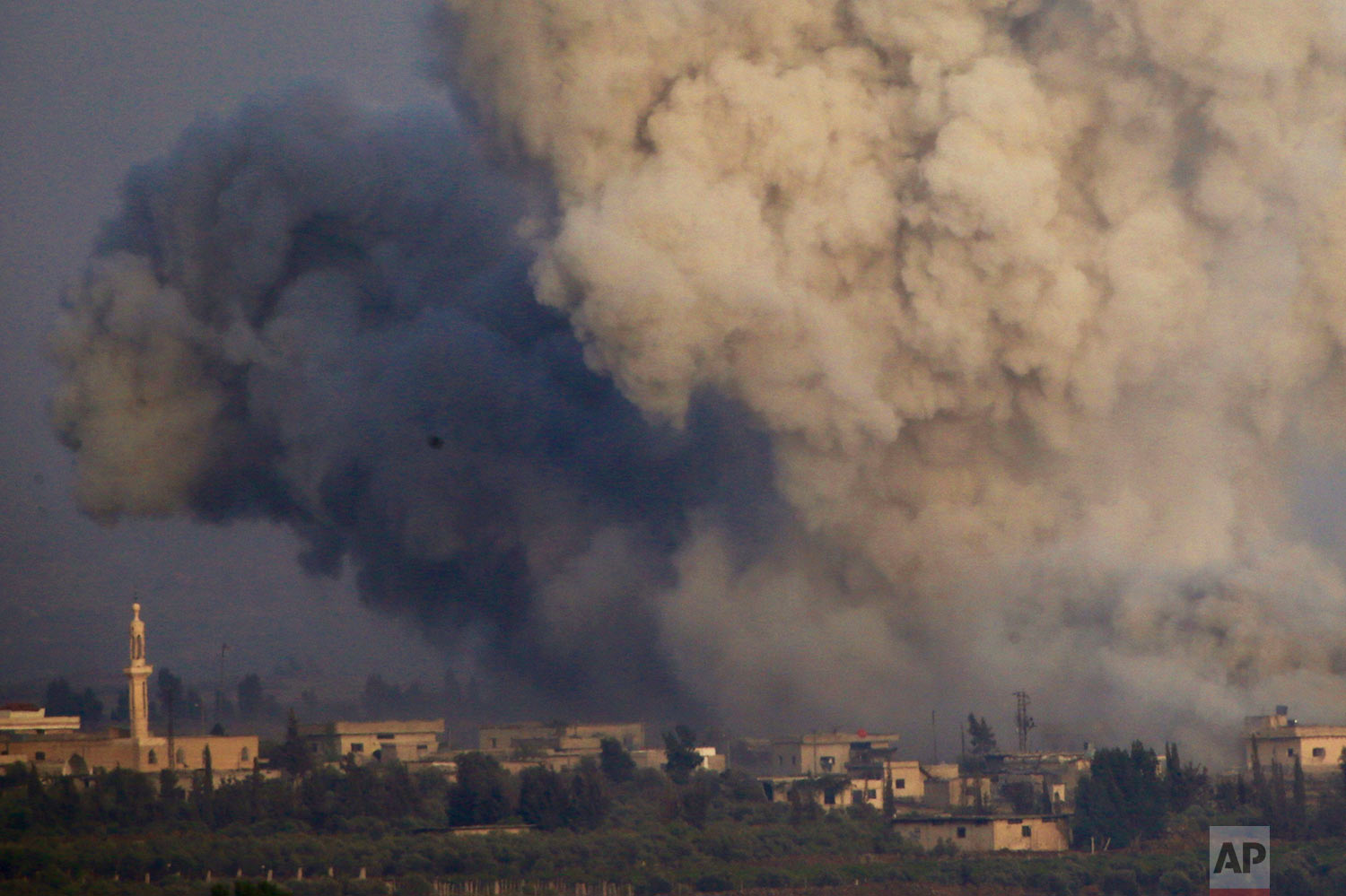Smoke and explosions from the fighting between forces loyal to Syrian President Bashar Assad and rebels in southern Syria as seen from the Israeli-controlled Golan Heights, Wednesday, July 25, 2018. (AP Photo/Ariel Schalit)