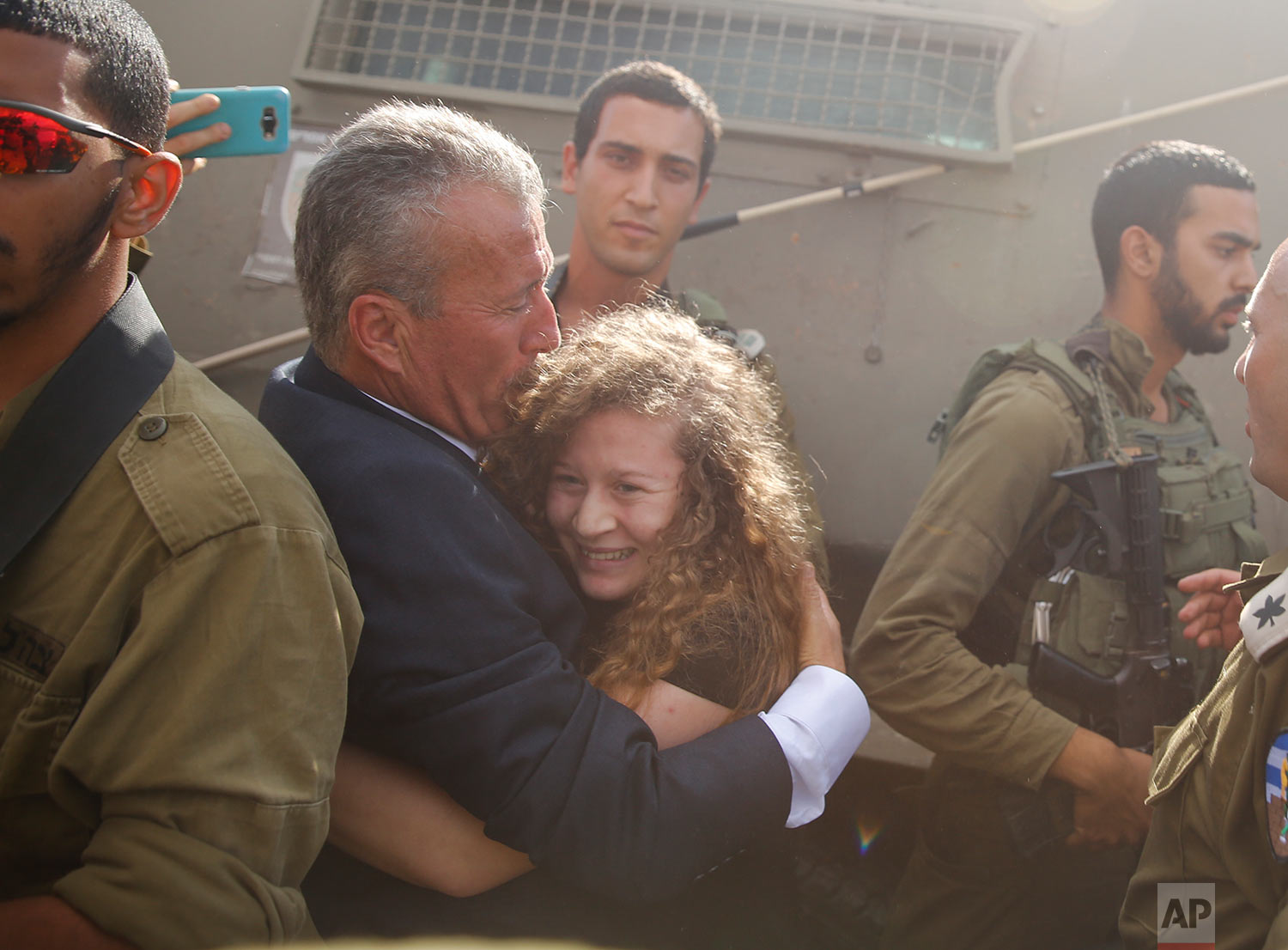 Ahed Tamimi is hugged by her father Bassem as she is released by the Israeli army Israeli prison after serving an eight month sentence at the entrance of her village of Nebi Saleh in the West Bank Sunday, July 29, 2018. (AP Photo/Nasser Shiyoukhi)
