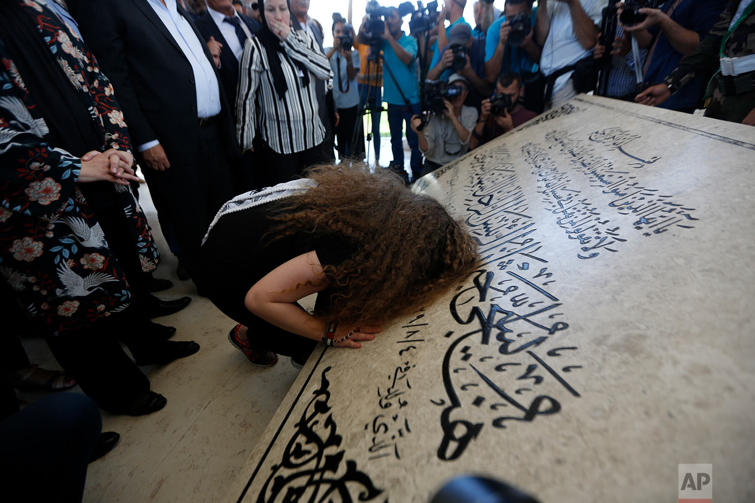 Ahed Tamimi prays at the tomb of former Palestinian leader Yasser Arafat in the West Bank city of Ramallah, Sunday, July 29, 2018. Palestinian protest icon Ahed Tamimi and her mother Nariman returned home to a hero's welcome in her West Bank village on Sunday after Israel released the 17-year-old from prison at the end of her eight-month sentence for slapping and kicking Israeli soldiers. (AP Photo/Majdi Mohammed)