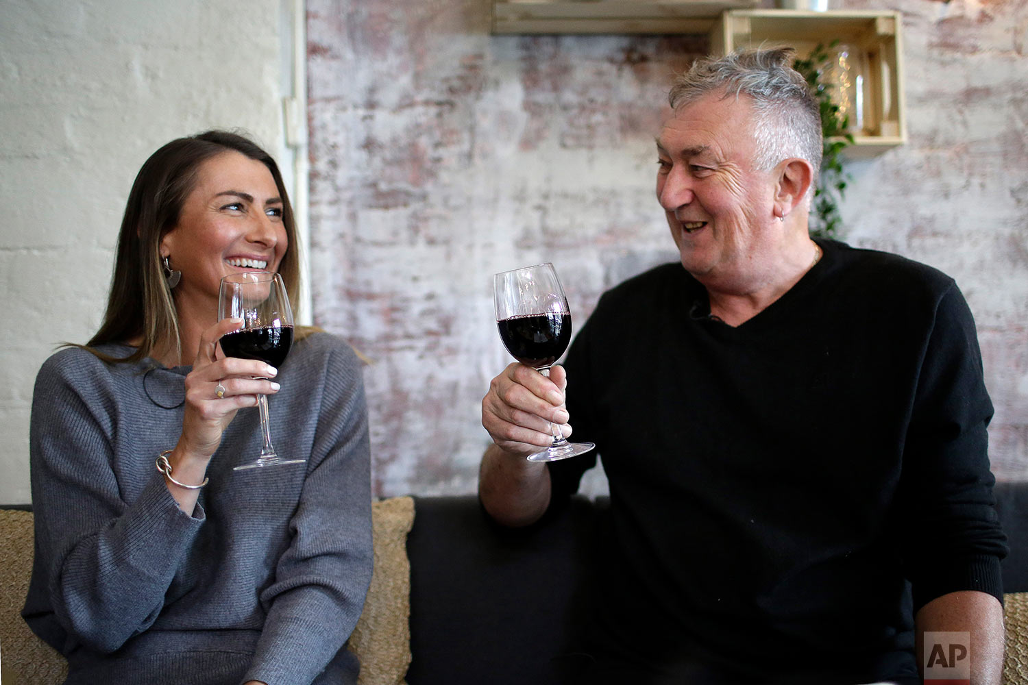 Peter Peacock, 68, right, and Gypsy Diamond, 36, share a laugh over a glass of Shiraz each, their favorite type of wine, in Melbourne, Australia. (AP Photo/Wong Maye-E)