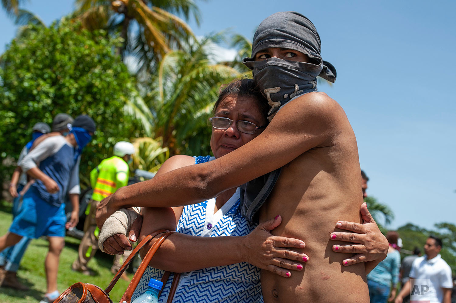 A masked, anti-government student who had taken refuge at Jesus of Divine Mercy church from an armed attack by police and government supporters is embraced by a relative after he was transported to the Cathedral with other students in Managua, Nicaragua, July 14, 2018. Cardinal Leopoldo Brenes negotiated with the president's office for the safe transfer of students out of the church and to the Metropolitan cathedral. (AP Photo/Cristobal Venegas)