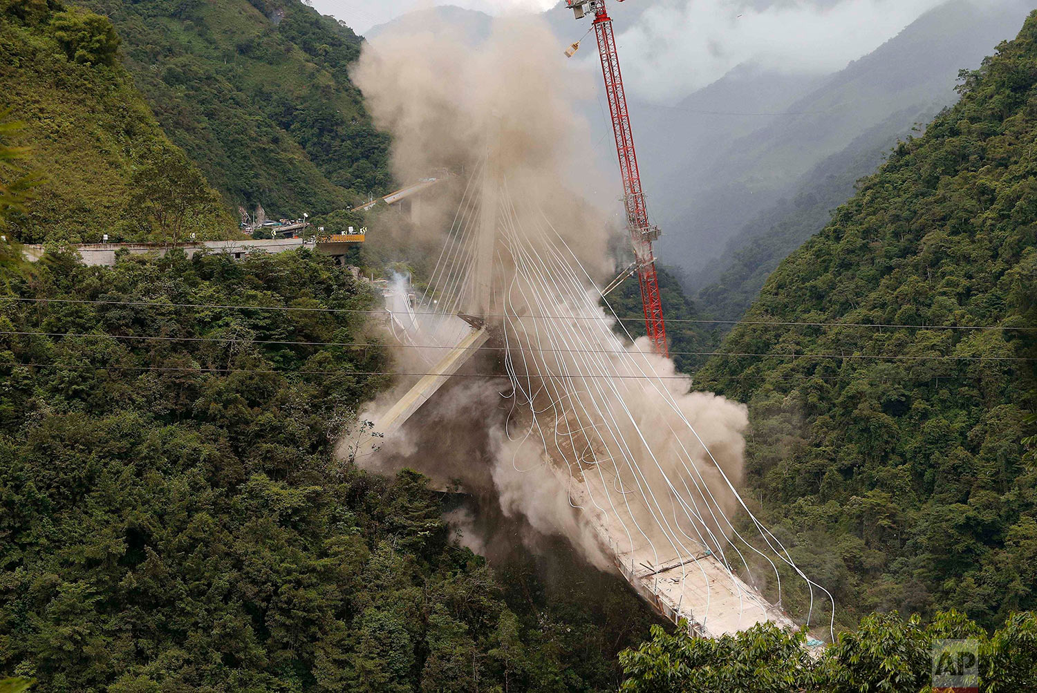 A partially-built suspension bridge is demolished by engineers in Chirajara, Colombia, July 11, 2018. One part of the bridge collapsed in January during its construction, killing at least nine workers. (AP Photo/Fernando Vergara)
